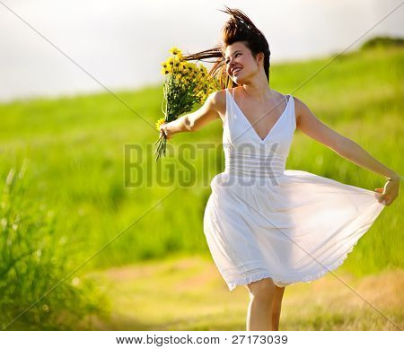 offene überspringen sorgenlos bengel Frau im Feld mit Blumen im Sommer Sonnenuntergang.