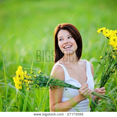 Adorable girl with flowers poses in a field during summer afternoon.