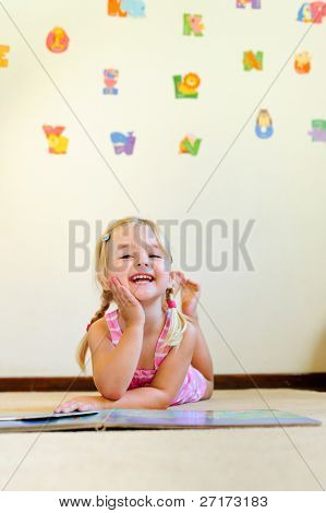 cute blonde girl with pigtails laughs and reads a book at kindergarten
