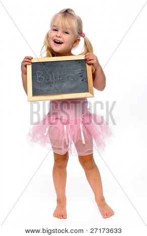 young ballerina smiling in studio holding ballet sign