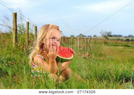 Cute blonde girl eats a watermelon in a field