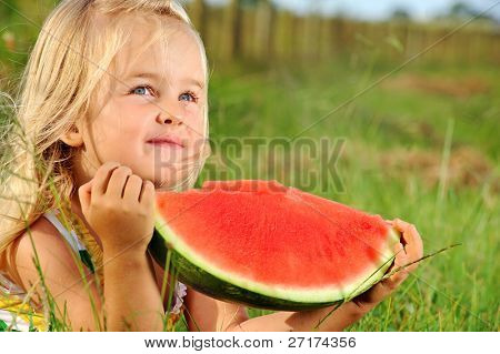 Adorable blonde girl eats a watermelon outdoors