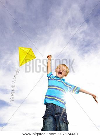 Young boy flies his yellow kite on a sunny day; a pictorial analogy for ambition
