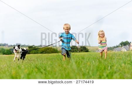 Young girl tries to catch up with her brother running ahead with their new puppy
