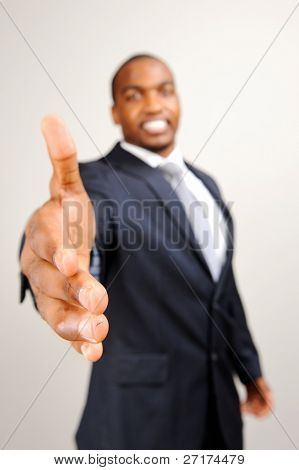 Black man in formal suit extends his hand out for a handshake, selective focus on hand