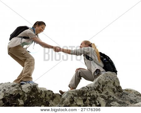 Hiker woman helps her friend climb up the last section of mountain. teamwork in outdoor lifestyle adventure
