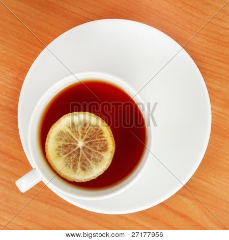 top plan of a tea cup with lemon on wooden table