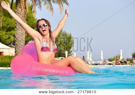 very happy woman no pink air bed in swimming pool