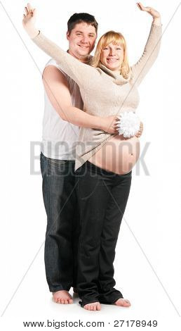 young husband is holding flower and hugging his pregnant wife