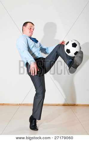 caucasian business man is playing football at office near white wall