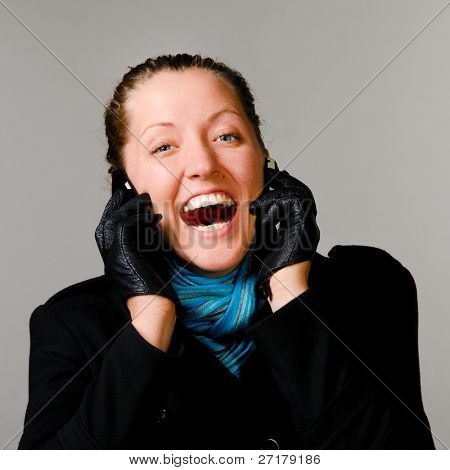 happy woman with two mobile phones in black coat on gray background