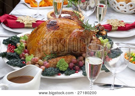 Holiday-decorated table, Christmas tree, champagne, and roasted turkey.