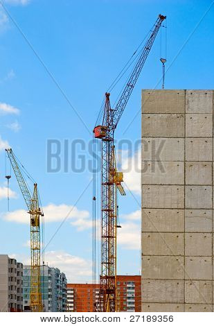 Building crane and building under construction against blue cloudy sky