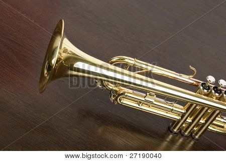 trumpet closeup on brown wooden background