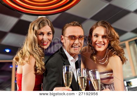 People with champagne in a bar having lots of fun