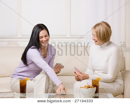 Adult mother and daughter playing cards and enjoying ice tea and snacks at home