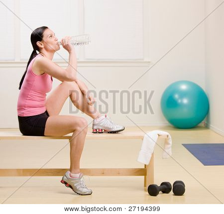 Woman drinking water and resting on bench in fitness studio
