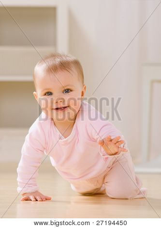 Close up of smiling baby crawling on livingroom floor [Approx. 8 mos]