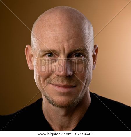 Close up studio shot of bald man with goatee and mustache