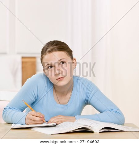 Teenage girl concentrating on homework assignment