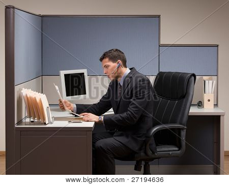 Serious young businessman with headset working at desk in cubicle