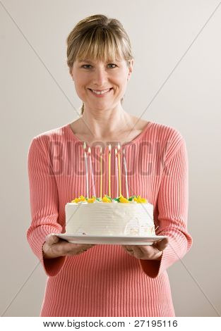 Generous woman holds birthday cake with lighted candles