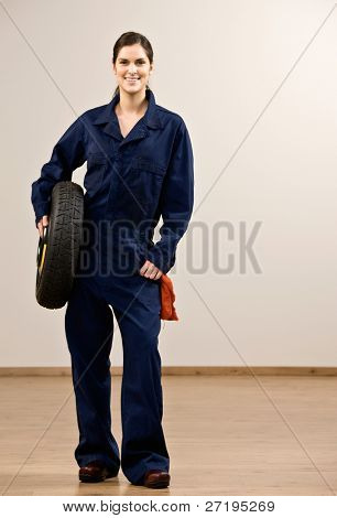 Smiling mechanic in coveralls holding tire