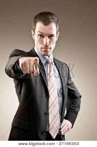 Authoritative, serious businessman pointing accusing finger