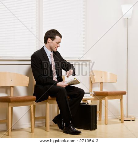 Businessman anxiously waiting for appointment or interview in office waiting area