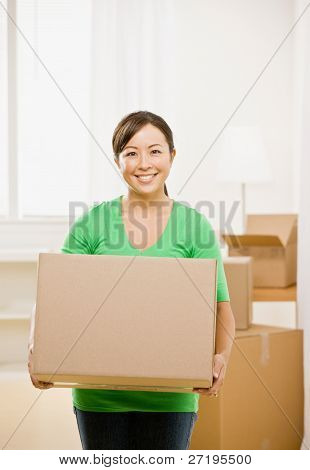 Happy woman moving into new home and carrying cardboard box