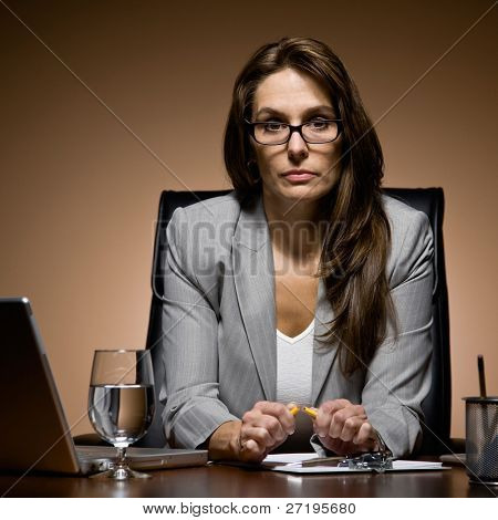 Angry and frustrated businesswoman working late at desk breaking pencil