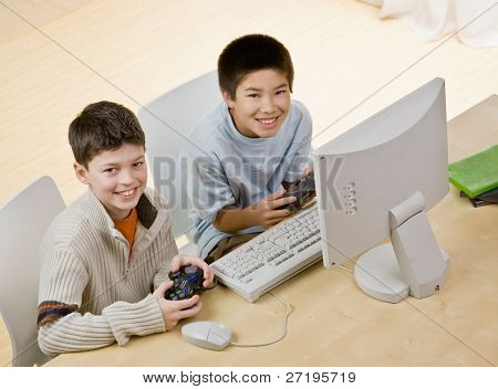 Friends holding video game controllers having fun playing video game on computer