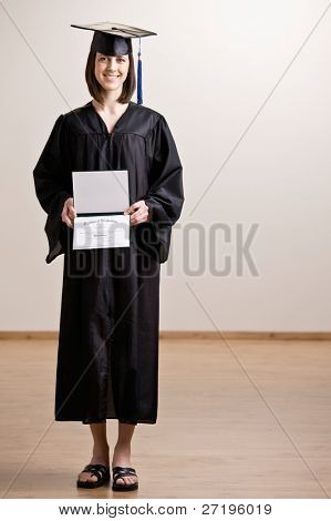 Confident graduating student wearing cap and gown holding diploma