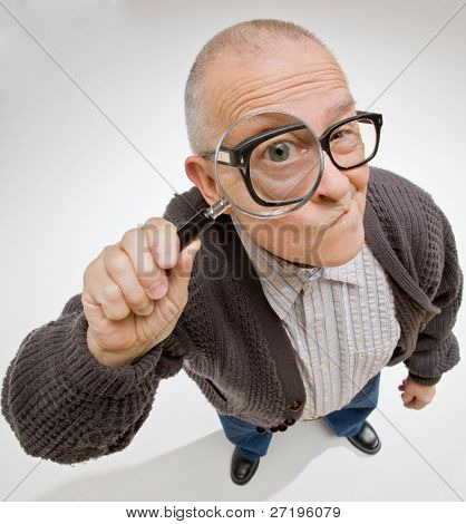 Curious man peering through magnifying glass