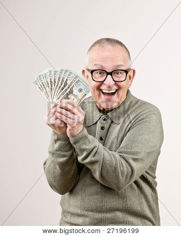Lucky, wealthy man excitedly holding group of twenty dollar bills