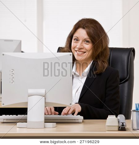 Confident businesswoman typing on computer at desk