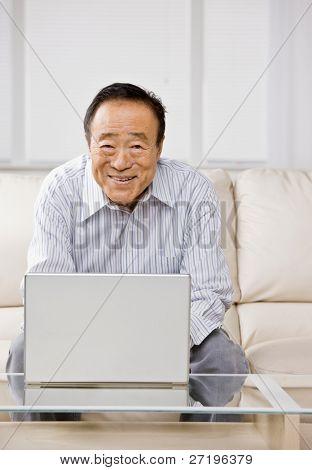 Man typing on laptop in livingroom