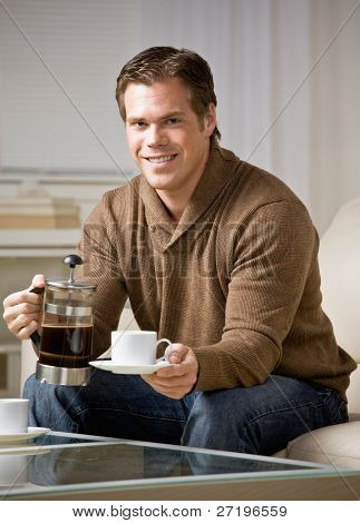 Man holding coffee carafe pouring cup of fresh coffee