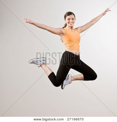 Strong athletic woman in sportswear jumping in mid-air