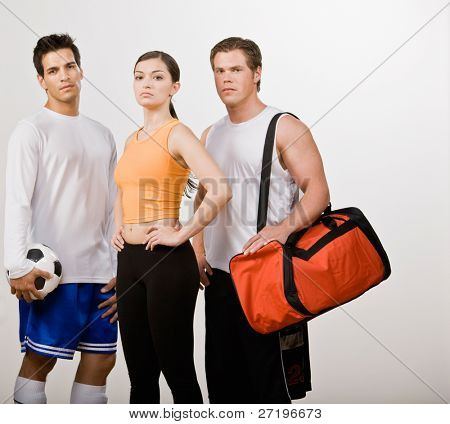Soccer player and athletic friends in sportswear with soccer ball and gym bag