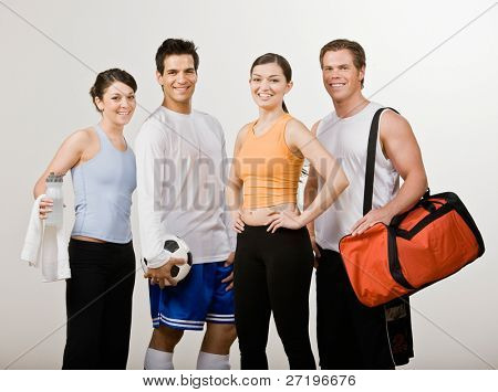 Soccer player and athletic friends in sportswear with soccer ball, gym bag and water bottle