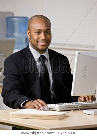 Happy businessman typing on computer at desk