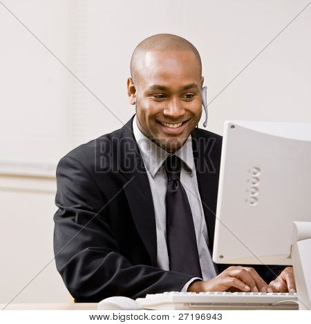Confident businessman talking on headset while typing on computer at desk