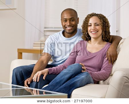 Relaxed couple hugging and sitting on sofa in livingroom