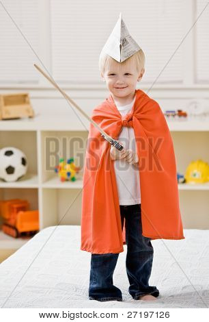 Boy wearing paper hat, cape and carrying a sword pretending to be a knight