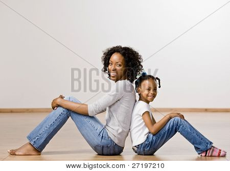 Madre feliz y relajada e hija sentado hacia atrás