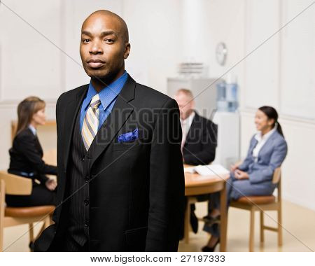 Confident businessman with co-workers in background