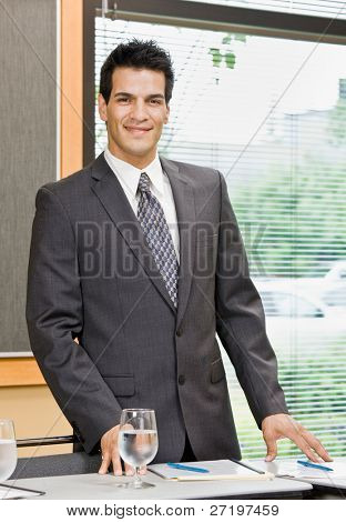 Confident businessman posing in conference room