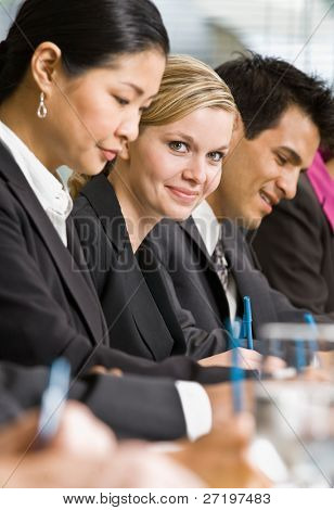 Multi-ethnic co-workers sitting in a row, writing at conference table