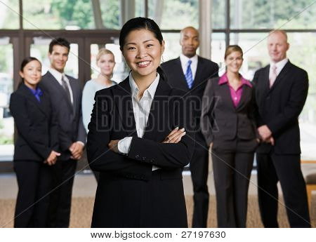 Confident Asian businesswoman posing in front of co-workers